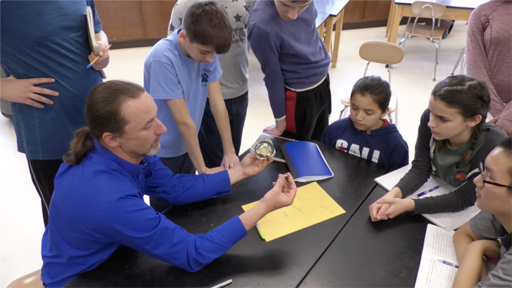 A make middle school teacher holds the components of a hand-build audio speaker as he speaks to several students around a table.