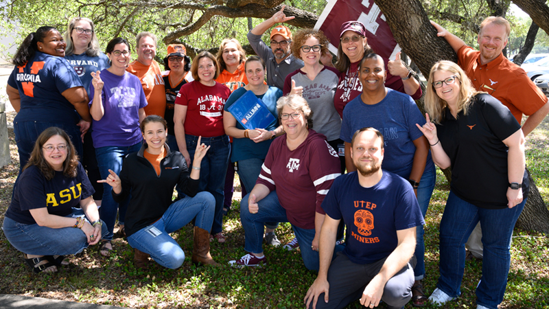 Approximately twenty members of the Dana Center Staff gather together in a group outdoors under a tree. Each staff member wears shirts or hats signifying their respective collegiate alma maters.